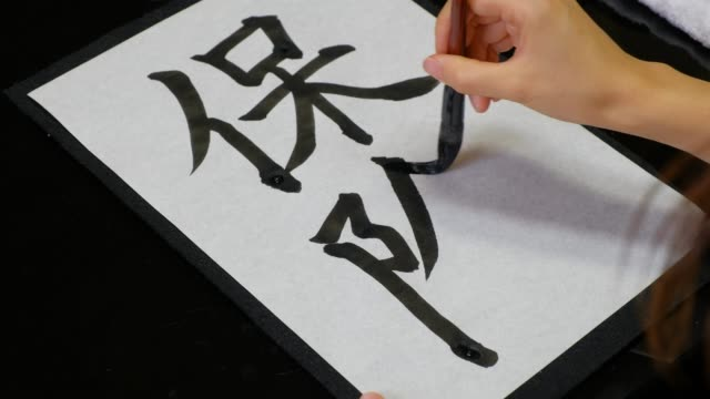 「保険」という言葉を書く日本人女性 - 習字点の映像素材/bロール