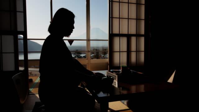 vídeos de stock, filmes e b-roll de mulheres japonesas no tradicional quimono bebendo chá perto de janela com mt.fuji, japão - cerâmica artesanato