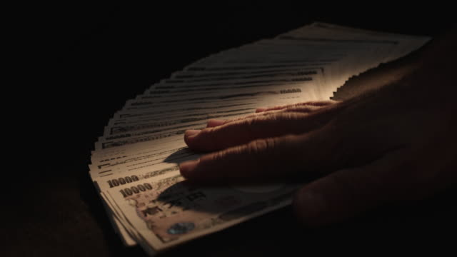 stockvideo's en b-roll-footage met japanse yen uitwaaierde op tafel, ondiepe focus - yenteken