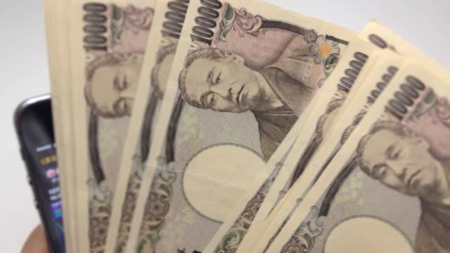stockvideo's en b-roll-footage met japanseyen met slimme telefoon - yenteken