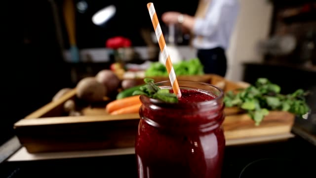 Jar of fresh beetroot smoothie with striped straw video
