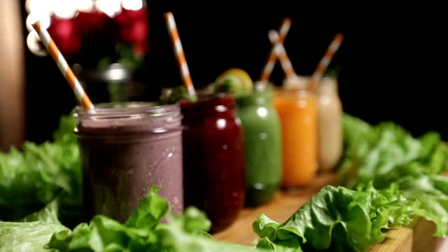 Jars of various smoothies with straws for dieting video