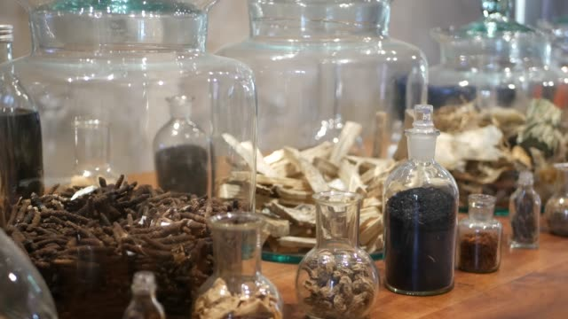 vídeos de stock e filmes b-roll de jars with dried herbs in apothecary shop. glass jars and bottles with assorted dried medicine herbs placed on shelf in retro oriental pharmacy - fitoterapia