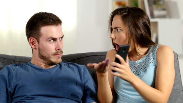 Jealous wife scolding her husband who is using phone Jealous wife scolding her husband who is using a smart phone at home girlfriend stock videos & royalty-free footage