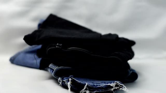 Jeans and plaid shirts falling on the table in a stack. Clothes for donation concept Jeans and plaid shirts falling on the table in a stack. Clothes for donation concept heap stock videos & royalty-free footage