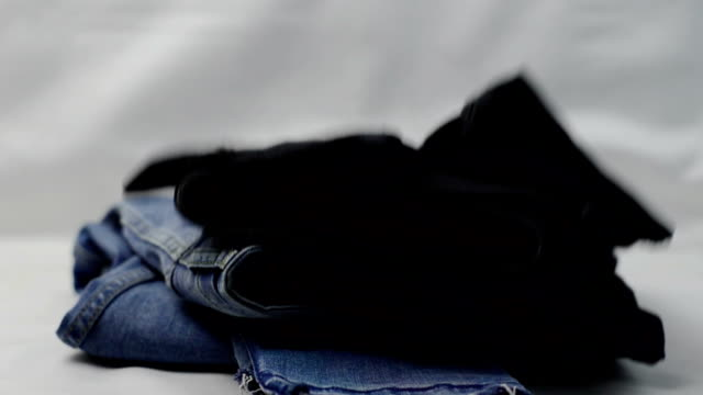 jeans and plaid shirts falling on the table in a stack. clothes for donation concept - mucchio video stock e b–roll
