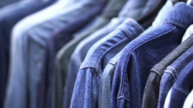jeans shirts hanging in variation denim tone. classic wear fashoin - dżinsy filmów i materiałów b-roll