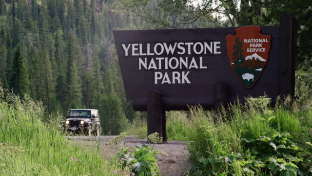 a jeep and motorcycles drive by the yellowstone national park welcome sign surrounded by forest and the rocky mountains - parco nazionale video stock e b–roll