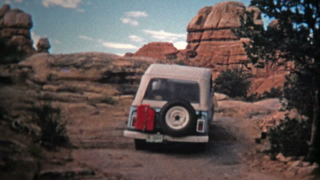 1971: Jeep driver bouldering up a steep incline offroad trail.