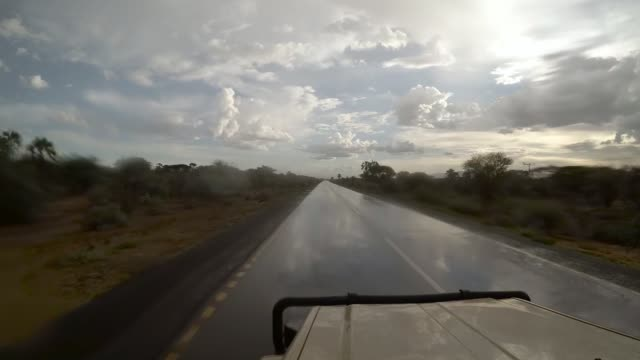Jeep driving along wet african road Jeep driving along wet african road tanzania stock videos & royalty-free footage