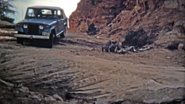 CANYONLANDS, UTAH -1971: Jeep driving down the famous silver stairs offroad trail and geological rock formation.