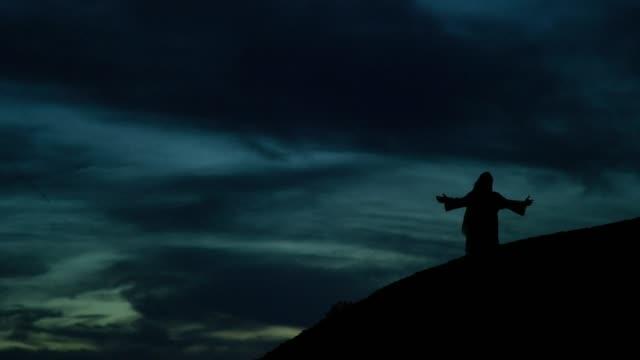 jesus kristus i silhouette prays medan knästående med armar ut på en sluttning utomhus på sunrise/solnedgång under en dramatisk cloudscape - korsform bildbanksvideor och videomaterial från bakom kulisserna