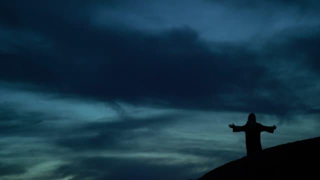 jesus kristus i silhouette går nedför en sluttning och droppar på knä för att be med armar ute utomhus vid sol uppgång/solnedgång under en dramatisk cloudscape - korsform bildbanksvideor och videomaterial från bakom kulisserna