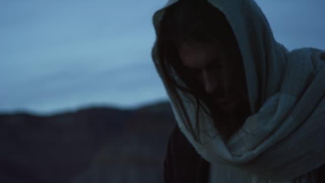 vídeos de stock e filmes b-roll de jesus christ kneels prays outdoors at sunrise/sunset outdoors - cristo redentor