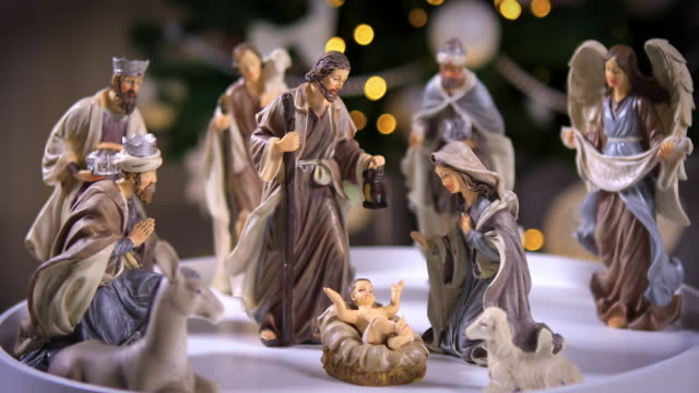 Jesus Christ Nativity scene in front of Christmas tree lights