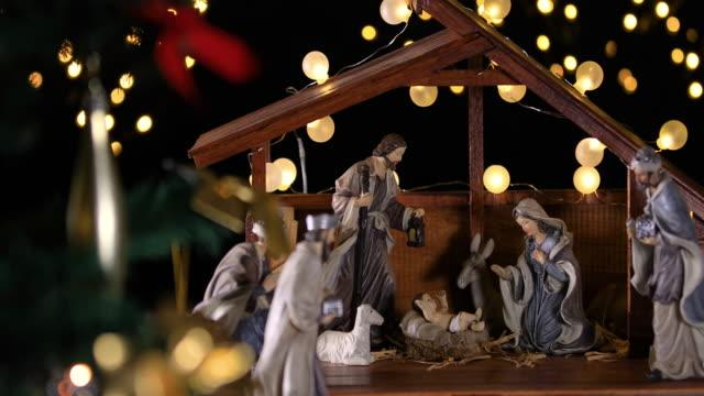 Jesus Christ Nativity scene with atmospheric lights near Christmas tree