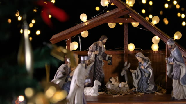 jesus christ nativity scene with atmospheric lights near christmas tree - christianity stock videos & royalty-free footage