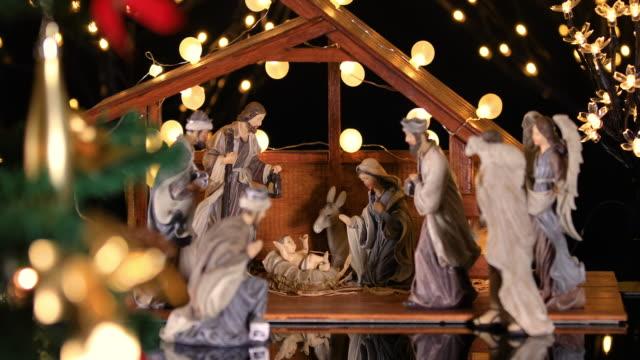 jesus christus krippe mit stimmungsvollen lichtern in der nähe des weihnachtsbaumes - religion stock-videos und b-roll-filmmaterial