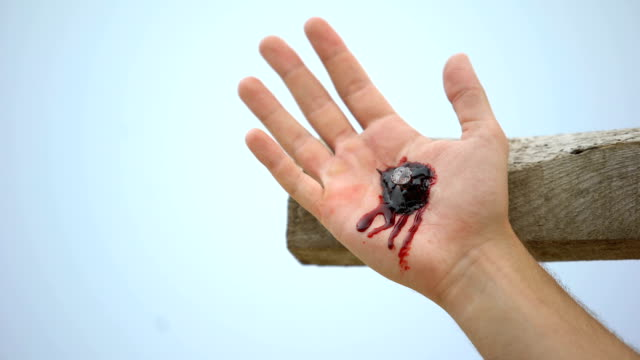 Jesus hand nailed to cross, clotted blood on wound, reenactment of crucifixion