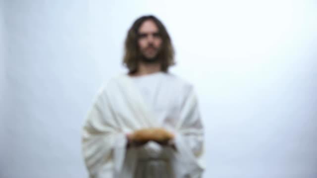 Jesús sosteniendo el pan sobre el fondo iluminado, la comida sacramental en las religiones - vídeo