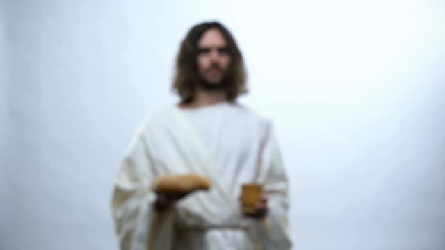 jesus holding wine and bread on illuminated background, christian ceremony - communion stock videos and b-roll footage