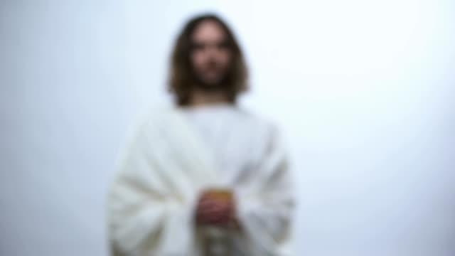 jesus holding wine on illuminated background, eucharist in catholic church - communion stock videos and b-roll footage