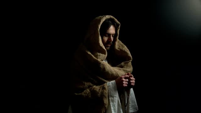 gesù che prega con rosario per le persone mortali pecca l'espiazione, la religione del messia - mitologia video stock e b–roll