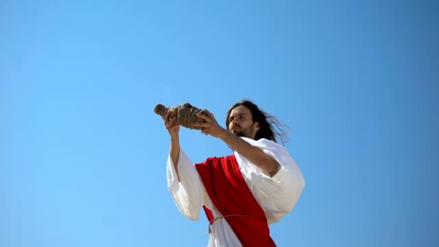 vídeos de stock, filmes e b-roll de jesus que levanta o vinho nas mãos ao céu, abençoando a bebida sacramental da eucaristia - primeira comunhão
