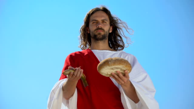 물고기와 빵, 성경 이야기, 수천 을 먹이에 대한 기적을 보여주는 예수 - 식빵 한 덩어리 스톡 비디오 및 b-롤 화면