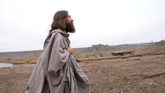 vidéos et rushes de jésus marchant le long de la route - peignoir