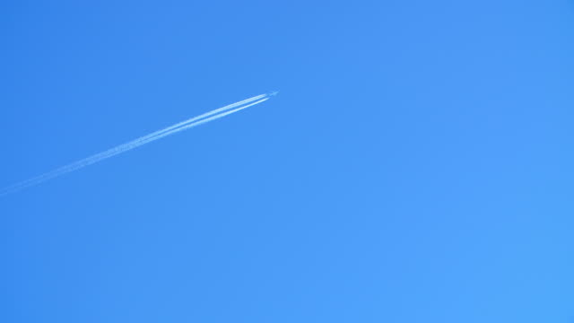 Jet airliner flying high in the sky leaves contrails in the clear blue sky. video