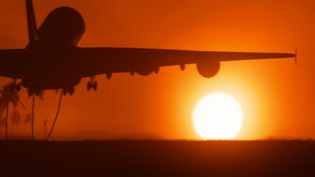 Jet airplane landing in Africa with big golden sunset sun