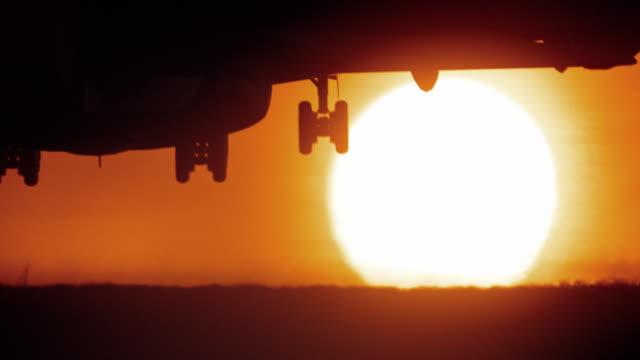 odrzutowy samolot pasażerski lądowania w afryce, z dużym złoty zachód słońca - lądować filmów i materiałów b-roll