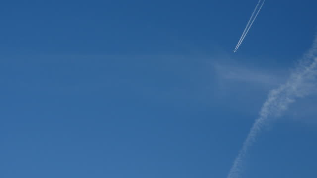Bидео Jet airplane with trail against the blue sky