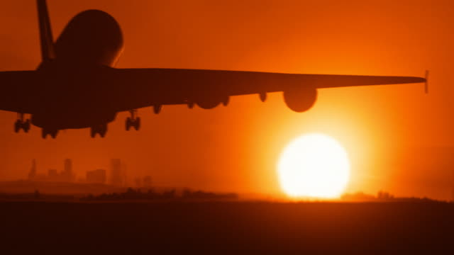 Jet landig in a city with sunset  - business travel
