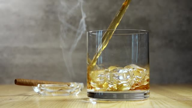 jet of whiskey in highball and cigar smoke. slow motion - sigaro video stock e b–roll