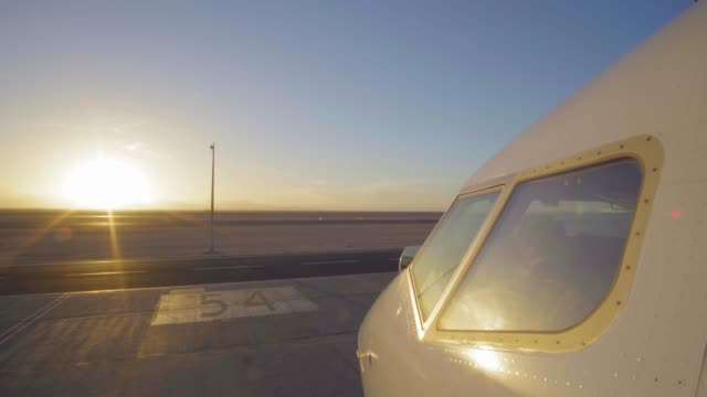 Jet plane in airport runway as silhouette in front of large sunset 4K UltraHD Jet plane in airport runway as silhouette in front of large sunset international match stock videos & royalty-free footage