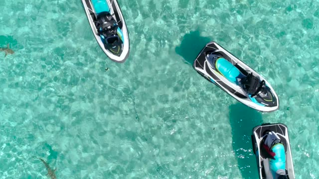 Jet ski in a blue lagoon in the Ocean. Enjoying amazing leisure activity in a paradise island. Perfect for tourism and holidays with beautiful view. Tropical travel concept - Close-up view with drone - 4K Aerial view of jet ski and boat sailing in a blue lagoon in the bay of Moorea island in French Polynesia. The beautiful island is in the Pacific Ocean, perfect for tourism and activities for amazing holidays. We can see jet ski jet skiing in the clear ocean next to Moorea island and his mountains, under the blue sky. The water is turquoise and clear and in the background, there is the Ocean. pacific islands stock videos & royalty-free footage
