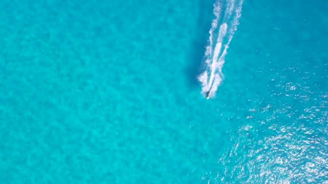 stockvideo's en b-roll-footage met jetski overhead antenne met prachtige turquoise blauwe water - blue sky