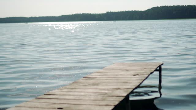 göl kenarında i̇skelesi ve glitter su - dalgakıran stok videoları ve detay görüntü çekimi