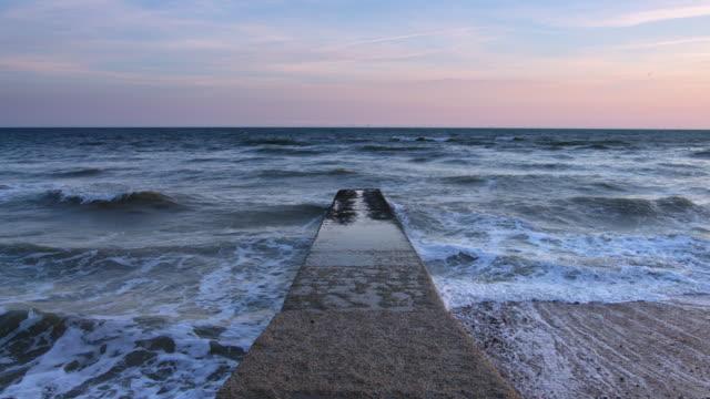 vídeos de stock, filmes e b-roll de cais, estendendo-se em ondas com distante eólico offshore - estreito mar