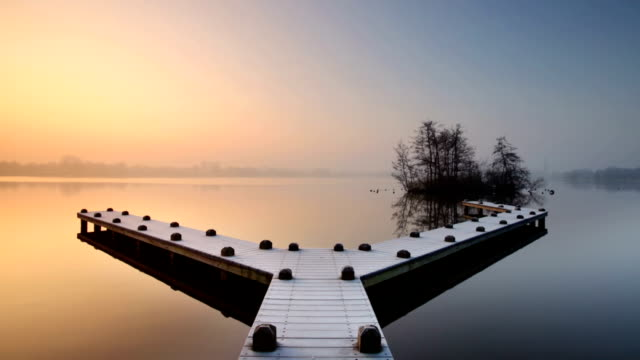 Jetty on a still lake on a foggy winter's morning video