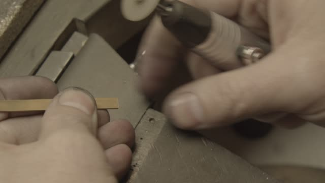 Jeweler polishes a gold piece with a small brush video