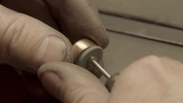 Jeweler polishes ring with a polishing wheel brush video