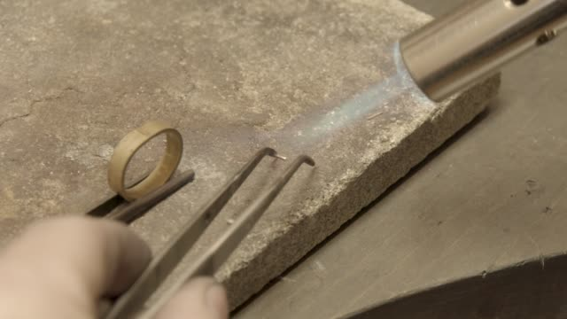 jeweler soldering pieces of gold on golden ring, tool preparation video