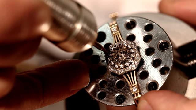 Jeweller hand polishing golden ring
