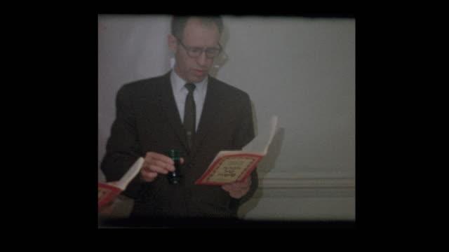 vídeos y material grabado en eventos de stock de pie de familia judía 1963 lectura hagadá en el seder de la pascua - pascua judía