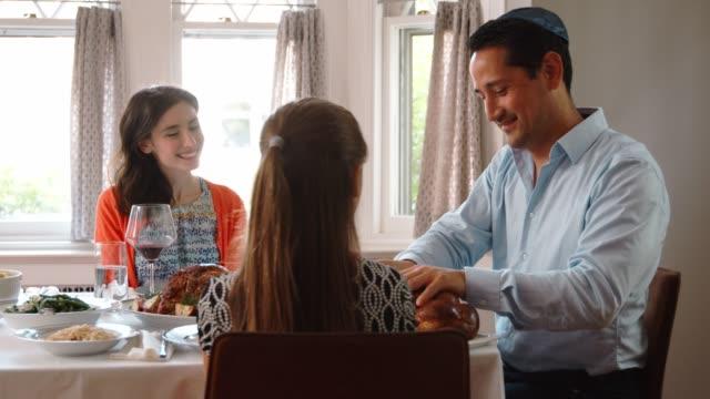 Jewish man sharing challah with family at Shabbat, close up video