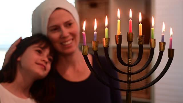 vídeos y material grabado en eventos de stock de madre e hija judías mirando una hermosa menorah en hanukkah vacaciones judías - hanukkah