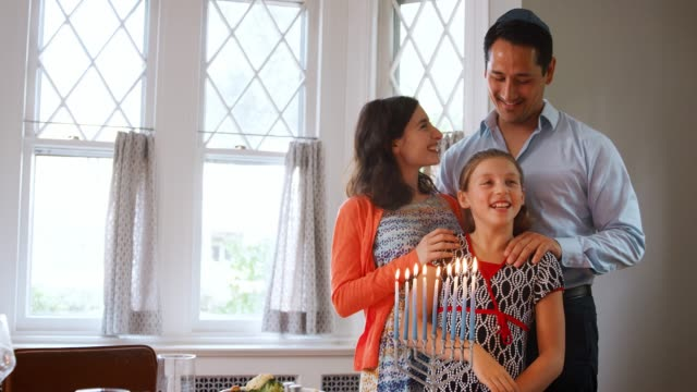 Jewish parents and daughter smiling, lit candles in menorah video
